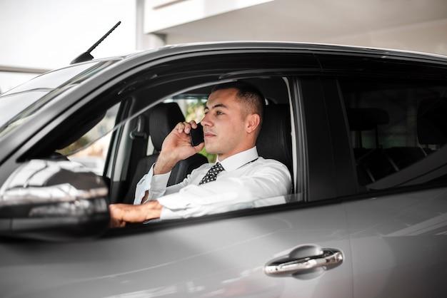 Negociante de carro de vista lateral falando por telefone Foto gratuita