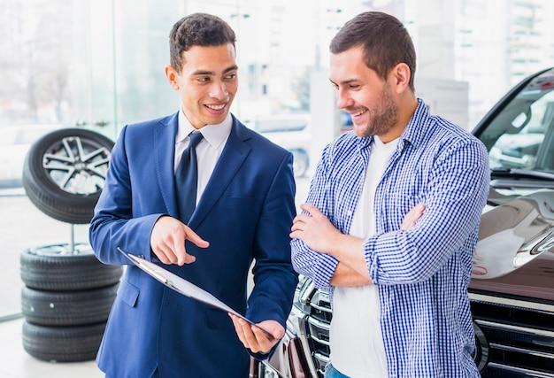 Negociante de carro falando ao cliente Foto gratuita