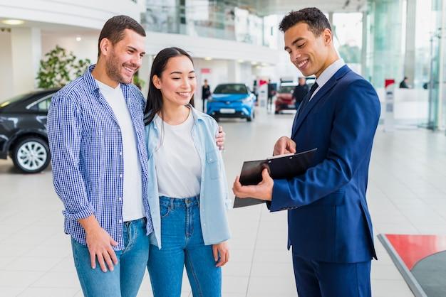 Negociante de carro falando com clientes Foto gratuita