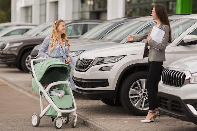 Negociante de carro fêmea que dá boas-vindas a um comprador Foto gratuita