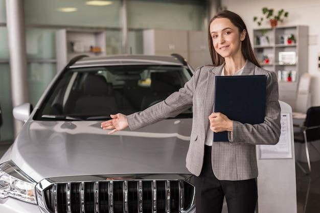 Negociante de carro feminino mostrando um carro Foto gratuita