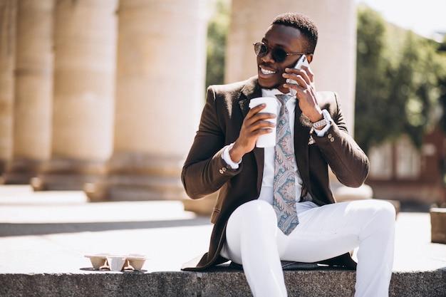 Negócio americano africano com café e telefone sentado nas escadas de um edifício Foto gratuita
