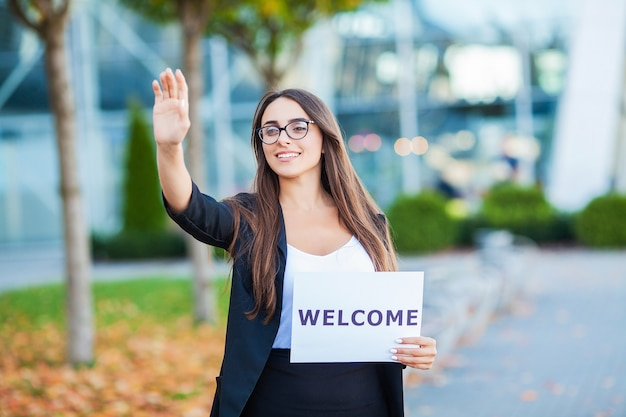 Negócio de mulheres com o cartaz com mensagem de boas vindas Foto Premium