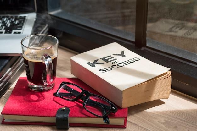 Negócio do livro do sucesso, dos vidros, do portátil e do café preto. Foto Premium