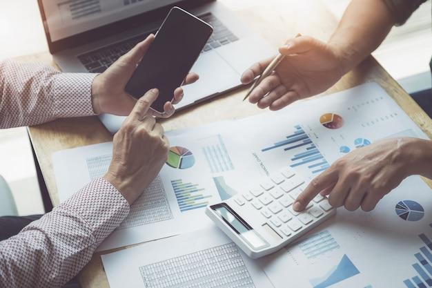 Negócio e parceria que discutem usando a calculadora para rever o anuário do balanço patrimonial com pena de terra arrendada e usar o laptop ao orçamento calculador. integridade de auditoria antes do conceito de investimento. Foto Premium