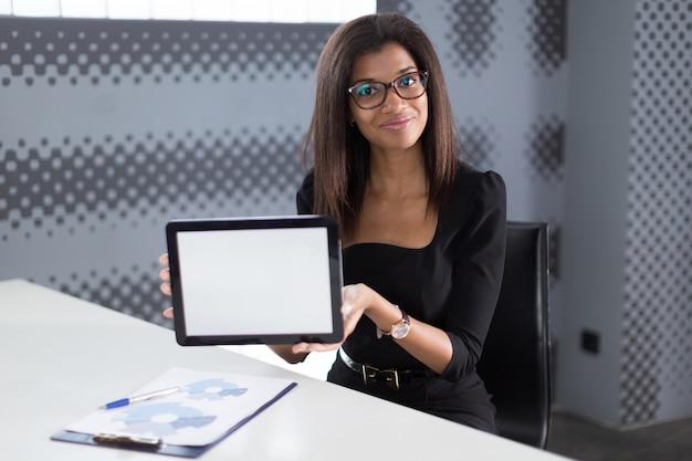 Negócio jovem atraente na suite forte preta sentar na mesa de escritório Foto Premium