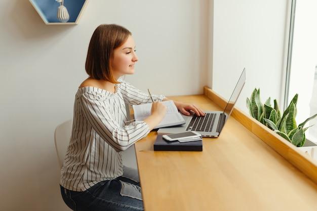 Negócio novo que datilografa no teclado e no trabalho do netbook com notas no livro de nota. Foto gratuita
