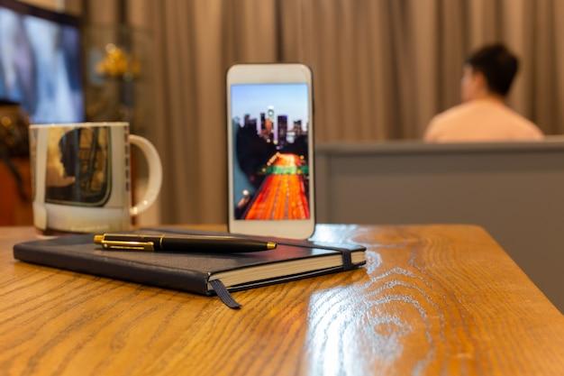 Negócio objeto celular com caderno e caneta na mesa de madeira Foto Premium