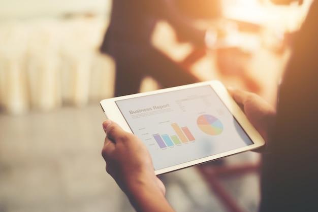 Negócio pessoa mão segurando estatísticas financeiras exibido em t Foto gratuita