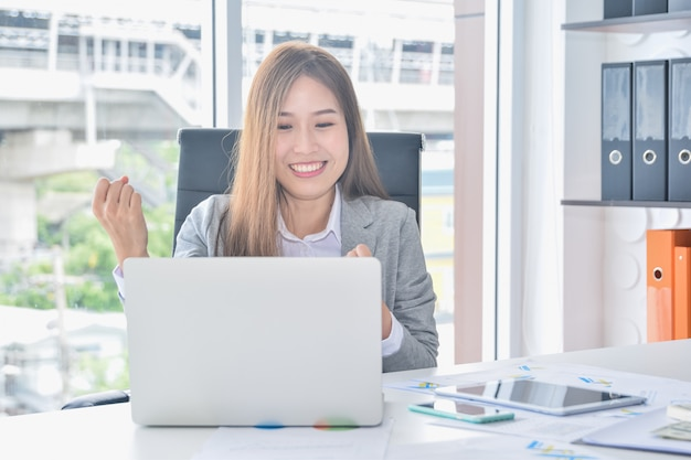 Negócios asiáticos, trabalhando com o laptop e ter sucesso aumentando os braços depois de receber boas notícias Foto Premium
