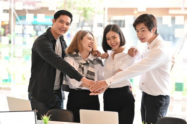 Negócios juntos, quatro jovens empresários com confiança e motivação relaxam no escritório moderno. Foto Premium