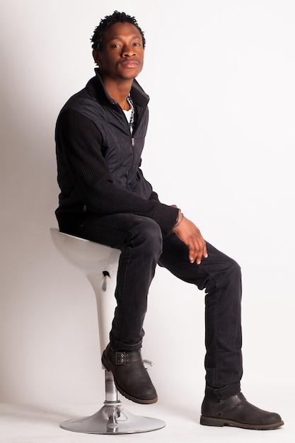 Negro bonito sentado em uma cadeira Foto gratuita