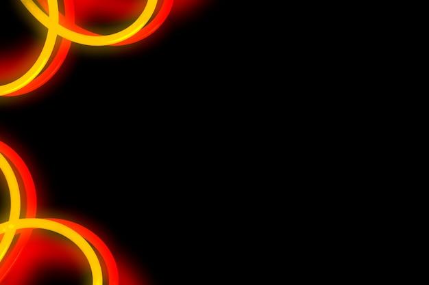 Néon vermelho e amarelo curvado design em fundo preto Foto gratuita