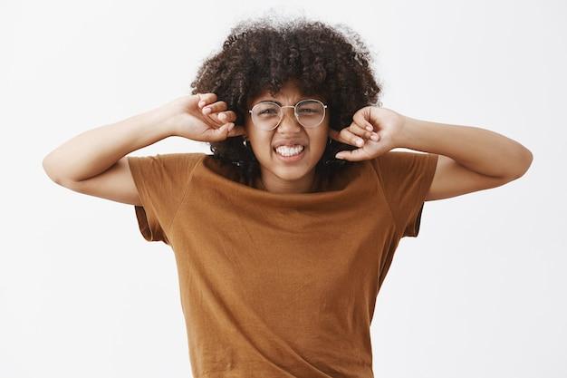 Nerd fofa e bonita com penteado afro em óculos transparentes, franzindo a testa e franzindo o nariz, cerrando os dentes de antipatia e desconforto cobrindo os ouvidos, não ouço som incomodativo Foto gratuita
