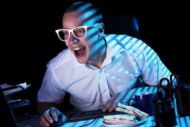 Nerd surfando a internet durante a noite Foto gratuita