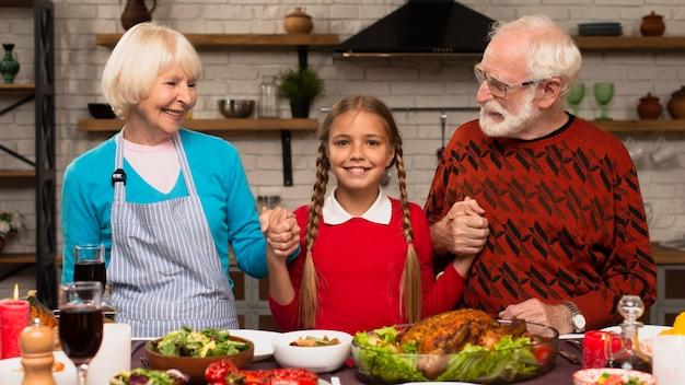 Neta, segurando seus avós e olhando para a câmera Foto gratuita