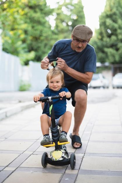 Neto aprendendo a andar de bicicleta Foto gratuita