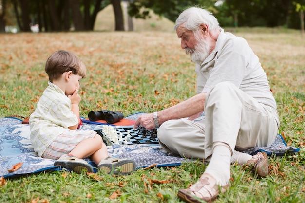 Neto com vovô no parque no piquenique | Foto Grátis