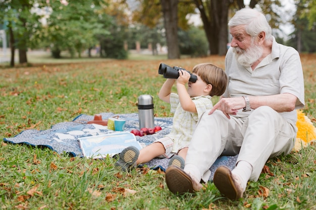 Neto com vovô olhando através do binóculo Foto gratuita