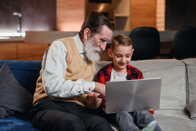 Neto está ensinando seu avô a usar o laptop. Foto Premium