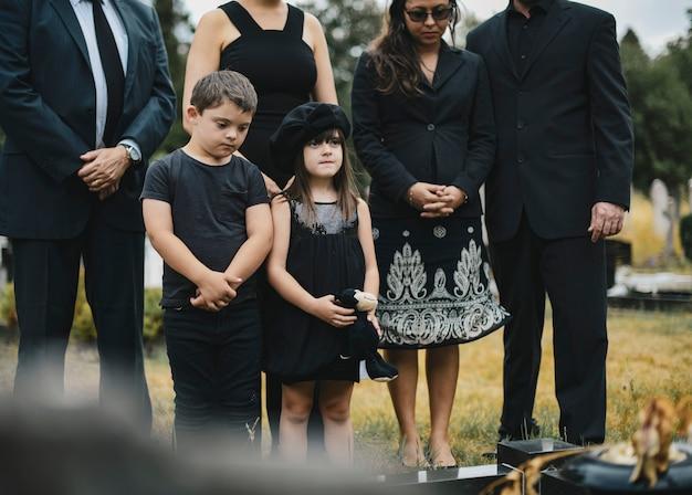 Netos tristes em pé junto ao túmulo Foto Premium