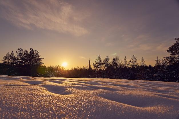 Neve em primeiro plano em uma noite gelada de inverno ao pôr do sol Foto Premium