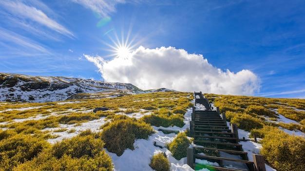 Neve, nuvens, montanhas, escadas e sol. Foto Premium