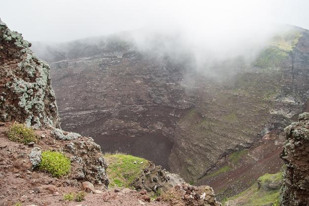 Névoa matinal, fumaça e cinzas no ar na cratera do monte vesúvio, nápoles, itália Foto Premium