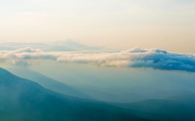 Nevoeiro, céus estão se movendo na montanha ao pôr do sol Foto Premium