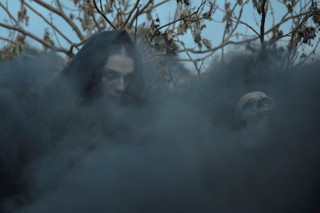 Nevoeiro witchy preto cobrindo o rosto e o crânio de mago Foto gratuita
