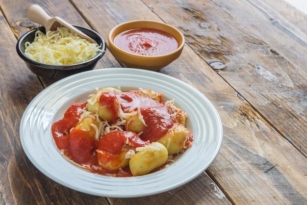 Nhoque recheado com pesto com molho de tomate caseiro e queijo Foto Premium
