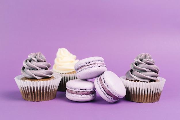 Nice macaroons perto de cupcakes Foto gratuita