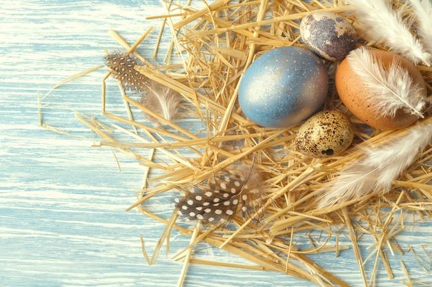 Ninho com ovos de páscoa na superfície de madeira azul, vista superior, com espaço de cópia Foto Premium