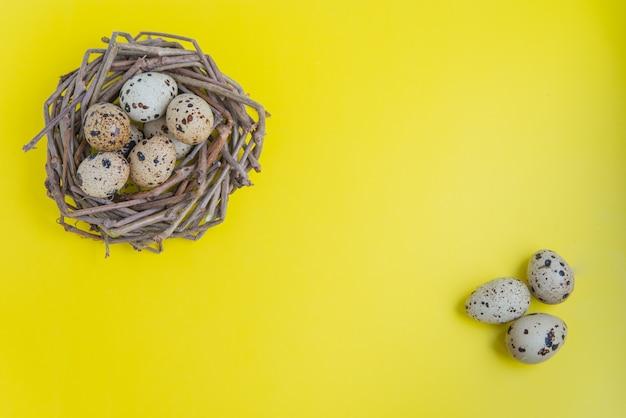 Ninho de codorna com ovos sobre o fundo amarelo. flatlay com espaço de cópia para cartões postais e design Foto Premium