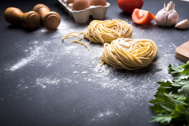 Ninho de massa de tagliatelle com ingredientes e peppermill sobre o balcão da cozinha Foto gratuita