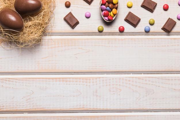Ninho de ovos de páscoa; chocolates e pedras preciosas na mesa de madeira com espaço para escrever o texto Foto gratuita