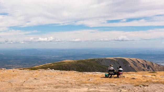 No alto do parque natural da serra da estrela, portugal com duas pessoas sem rosto, de costas e sentadas a observar a beleza da paisagem, sem rosto, de costas Foto Premium