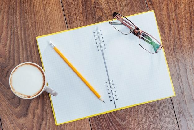No caderno de madeira lápis, café e flores. Foto Premium