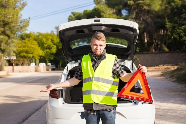 No caso do homem com problemas com um carro, ele recebe uma placa triangular vermelha de emergência Foto Premium