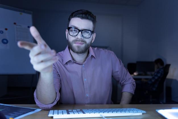 No computador. homem barbudo alegre e positivo sentado à mesa e olhando para você enquanto trabalha no computador Foto Premium