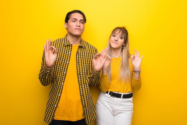 No dia dos namorados casal jovem sobre fundo amarelo vibrante em pose de zen Foto Premium
