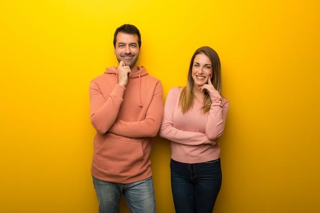 No dia dos namorados grupo de duas pessoas no fundo amarelo sorrindo com uma expressão doce Foto Premium