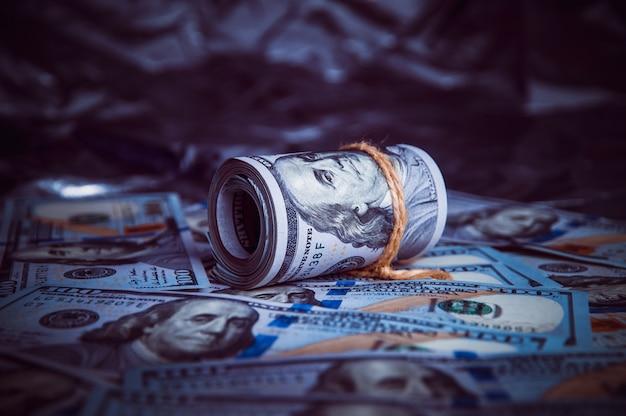 No escuro em dinheiro quebrado é um rolo de dólares. Foto Premium
