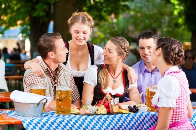 No jardim da cerveja - amigos em uma mesa com cerveja Foto Premium