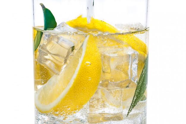 No jarro é uma bebida de gelo, os lóbulos de um limão suculento amarelo fresco e água cristalina. Foto Premium
