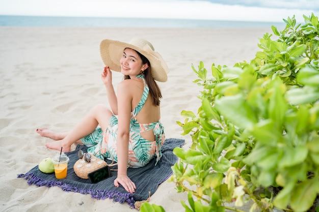 No verão, mulher bonita asiática usando um vestido está sentado e tocar um telefone inteligente Foto Premium