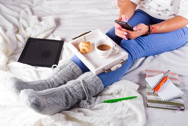 Noite aconchegante, meias quentes de lã, cobertor macio, velas. mulher relaxando em casa, bebendo cacau, usando o laptop. estilo de vida confortável. Foto Premium