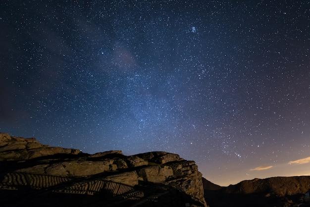 Noite nos alpes sob o céu estrelado e as majestosas falésias rochosas nos alpes italianos Foto Premium