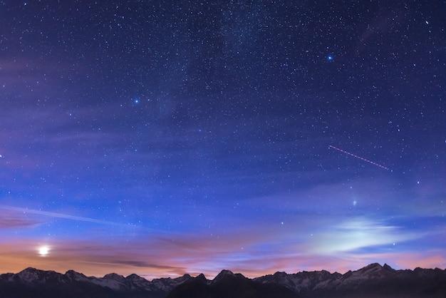 Noite nos alpes sob o céu estrelado e o luar Foto Premium