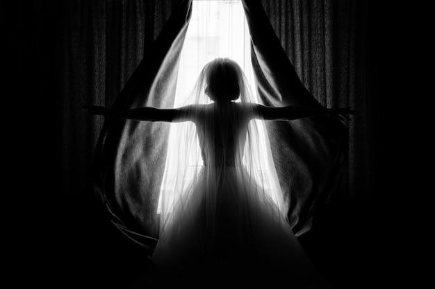 Noiva abre as cortinas no quarto de hotel Foto gratuita